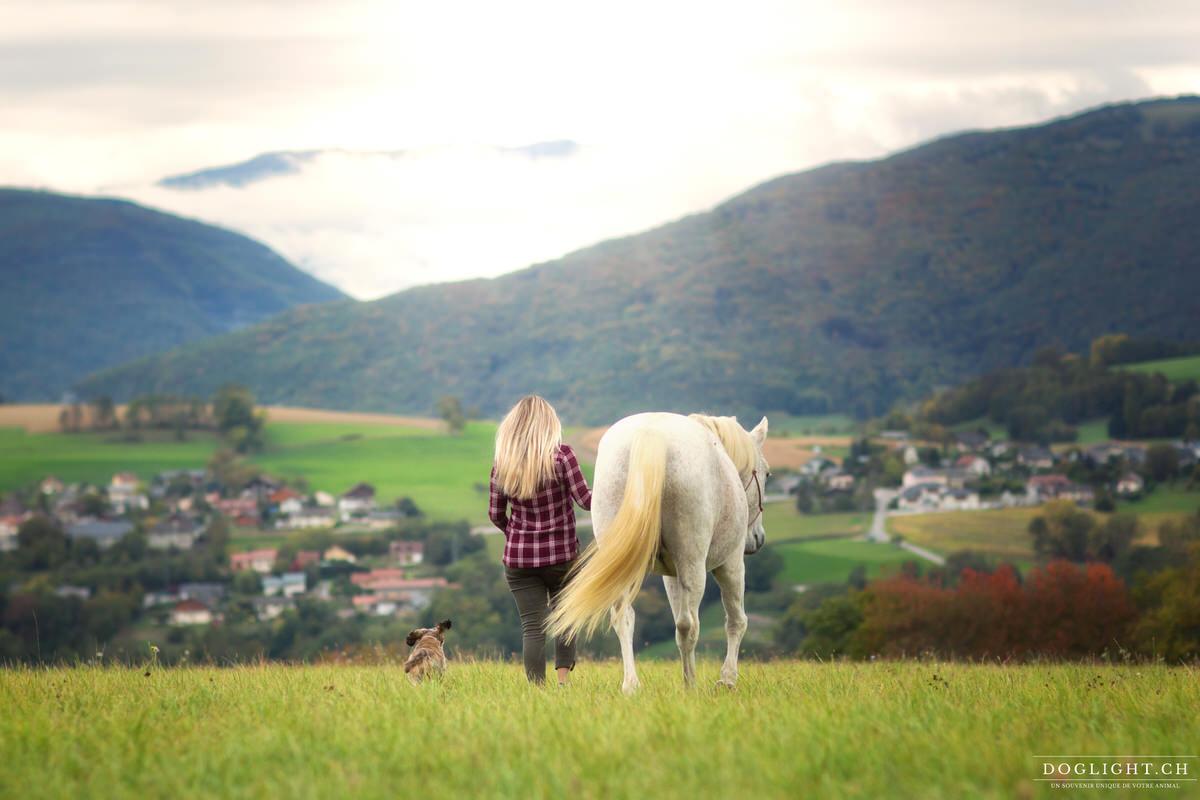 Femme qui part avec son cheval et son chien face aux montagnes