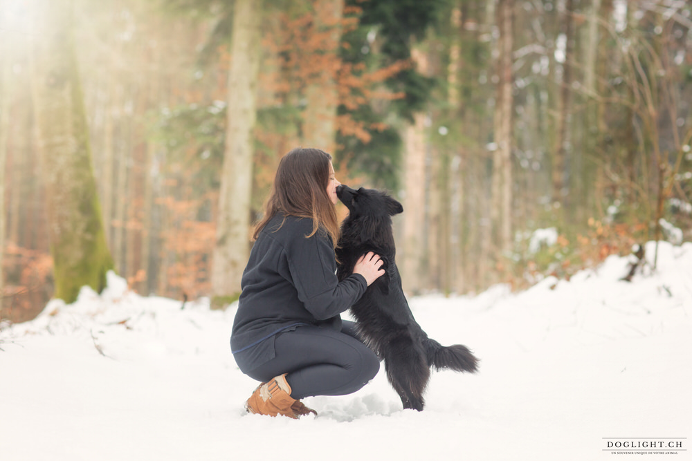 Portrait fille et son chien noir dans la neige